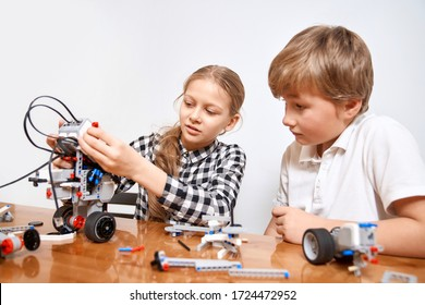 Front view of boy helping girl in creating robot using building kit for kids on table. Nice interested friends smiling, chatting and working on project together. Concept of science engineering.
