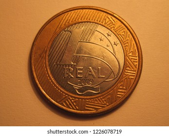Front view of Brazilian coin. 1 real from Brazil. Great for numismatic collection. Shiny coin isolated on yellow surface of paper.