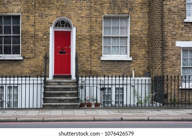 Front view of british orange brick house facade with red door and sidewalk in front