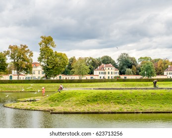 Front view of buildngs of Nymphenburg palace near center of Munich in Germany, under cloudy sky, with unrecognized tourists