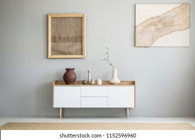 Front view of burlap artworks on a light gray wall above a wooden cupboard with decorations in real photo of a living room interior with a place for your armchair
