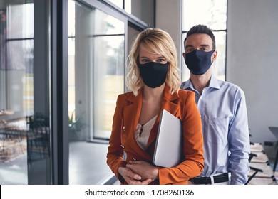 Vorderansicht von Geschäftsleuten, die während der Quarantänezeit im Büro Schutzmasken tragen