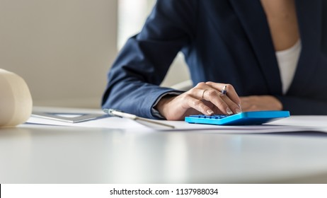 Front view of business woman doing a calculation on a blue manual calculator.