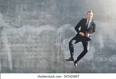 Front view of a businessman jumping up high to click his heels