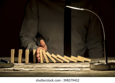 Front view of businessman stopping falling dominos with his hand on wooden textured office desk with a lamp turned on.