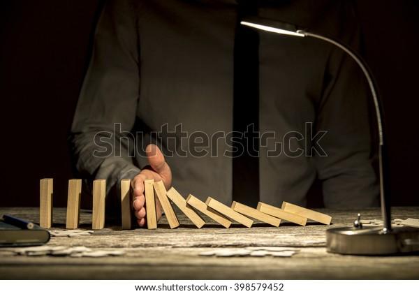 Вид спереди бизнесмена, останавливающего падение домино рукой на деревянном фактурном офисном столе с включенной лампой.