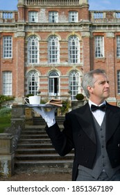 Front view of a butler holding up a tray containing a cup of tea and a newspaper in front of a huge manor house on a bright, sunny day