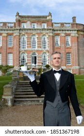 Front view of a butler holding up a tray containing a newspaper and a cup of tea in front of a huge manor house on a bright, sunny day