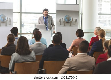 Front view of Caucasian businessman with laptop speaks in front of diverse group of business people sitting at business seminar in office building