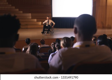 Front view of Caucasian businessman sitting on a wheelchair and giving presentation to the audience in the auditorium