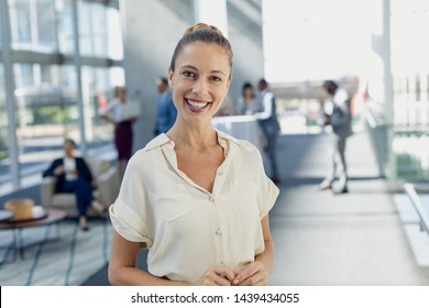 Front view of Caucasian female executive looking at camera while standing in modern office. Behind her, colleagues interacting with each other.