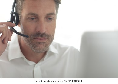 Front view of Caucasian male customer service executive talking on headset at desk in a modern office