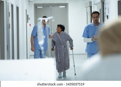 Front view of Caucasian male doctor interacting with disabled female patient in the corridor at hospital