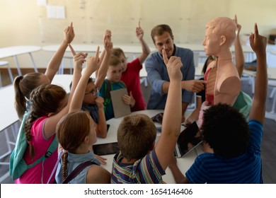Front view of a Caucasian male teacher using a human anatomy model to teach a diverse group of elementary school children during a biology lesson, the children sitting in a circle and raisinbg their