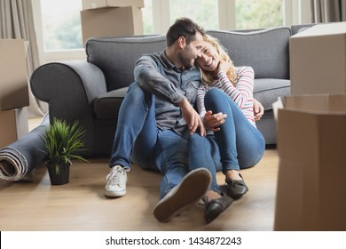 Front view of Caucasian romantic couple sitting on the ground together in new home.