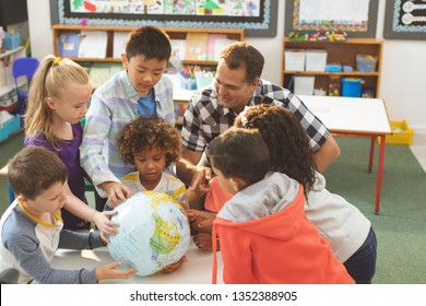 Front view of a Caucasian schoolteacher interacting with his pupils over a earth globe putting on a table in classroom at school