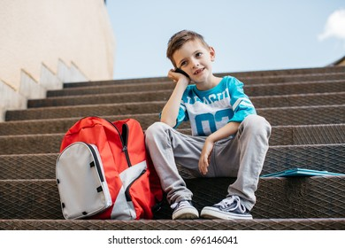 Front view of a cheerful student calling from his mobile outside school
