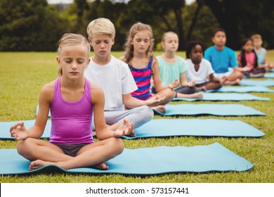 Front view of children doing yoga in the park