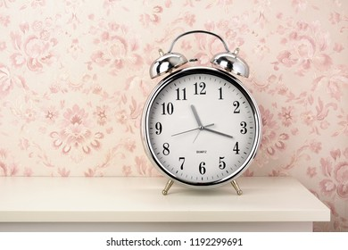 Front view of a chrome retro alarm clock on mantelpiece, wallpaper with design