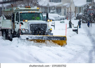 Front view of city services snow plow truck with yellow push blade clearing covered roads after heavy winter snow fall and passing by children bundled in warm clothes playing while flakes still fall.