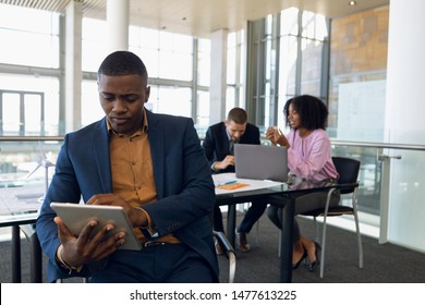 Front view cloe up of young African American businessman sitting using tablet computer in an office. A Caucasian businessman and an African American businesswoman work sitting at a desk in the