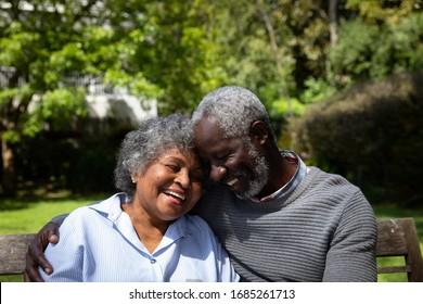 Front-View, Nahaufnahme des älteren afroamerikanischen Ehepaars im Garten, sitzend auf einer Bank, umarmt und lächelt. Familie genießt Zeit zu Hause, Lifestyle-Konzept
