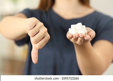 Front view close up of a woman hand holding sugar cubes with thumbs down at home
