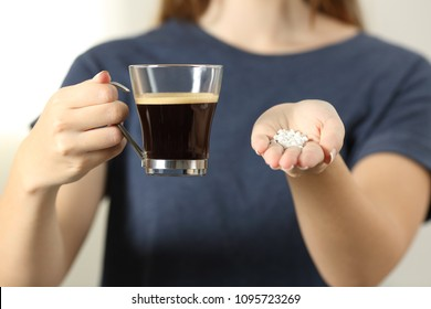 Front view close up of a woman hands holding a coffee cup and saccharin pills