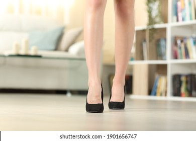 Front view close up of woman legs with high heels walking in the living room at home