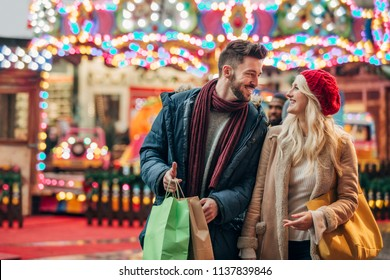 Front view, close-up, of a couple walking along a city street during winter after shopping in the sales.