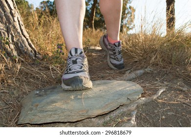 front view of closeup of feet of sportswoman walking along the path in the mountain