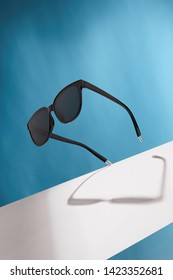 Front view closeup shot of wayfarer-shaped sunglasses with raven black rim and lenses. The tilted accessory is isolated in air over the background with wide white stripe. Stylish summer fashion item.