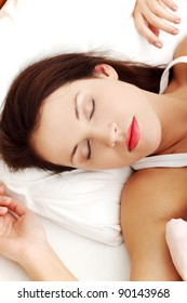 Front view closeup of a young beautiful woman sleeping in the bed, resting her hands next to her face.