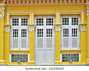 Front view of colorful exterior of a traditional Straits Chinese or Peranakan vintage shop house with antique wooden shutters and yellow facade in afternoon sunlight in Joo Chiat Singapore
