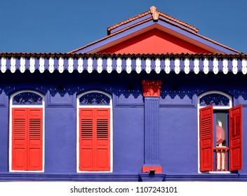 Front view of colorful heritage Singapore shop house with blue exterior, antique red louvered shutters and arched windows in historic Little India