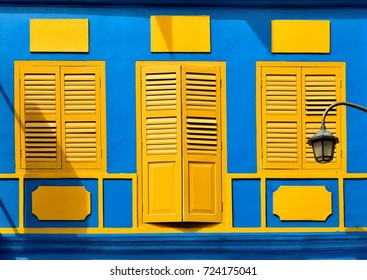 Front view of colorful vintage Straits Chinese or Peranakan shop house  exterior with antique yellow wooden louvered shutters and blue exterior in the historic Chinatown District of Singapore