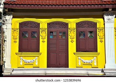 Front view of colourful exterior of a traditional Straits Chinese or Peranakan vintage shop house with antique wooden shutters and yellow facade in afternoon sunlight in Little India Singapore