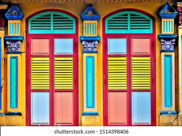 Front view of colourful traditional vintage Singapore Straits Chinese or Peranakan shop house with ornate exterior, antique wooden louvered shutters and arched windows in historic Little India.