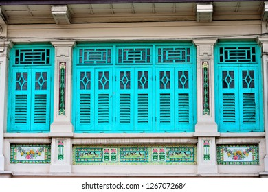 Front view of colourful vintage traditional Singapore Peranakan or Straits Chinese shop house exterior with antique blue wooden shutters in historic Chinatown.