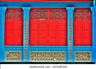 Front view of colourful vintage traditional Singapore Peranakan or Straits Chinese shop house exterior with antique red wooden shutters blue exterior and Chinese tiles in historic Geylang