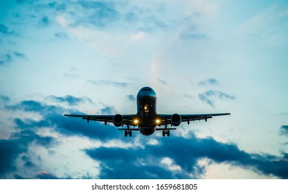 Front view of a commercial airplane with turned on landing lights landing on an airport.