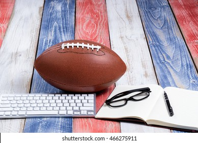 Front view of computer keyboard, reading glasses, notepad, pen and American football on red, white and blue rustic wooden boards. Concept of draft and plays for the season.