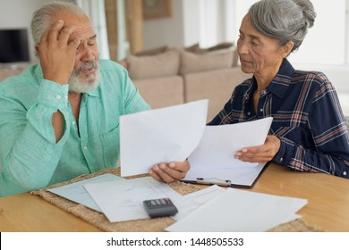 Front view of concerned African-American couple doing finances on the table indoor. Authentic Senior Retired Life Concept