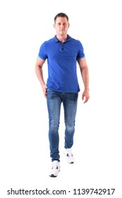 Front view of confident young adult man walking forwards and looking at camera in blue polo shirt. Full body isolated on white background.