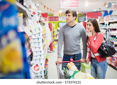 Front view of couple choosing products at grocery store