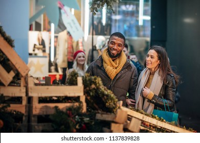 Front view of a couple looking at a christmas market to buy a wreath.The market stall is on a city street.