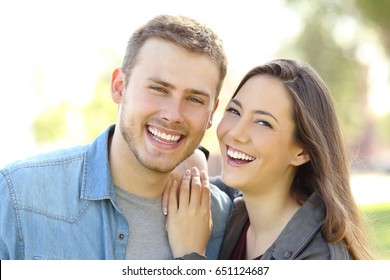 Front view of a couple posing outdoors with perfect smile and white teeth and looking at you in a park with a green background