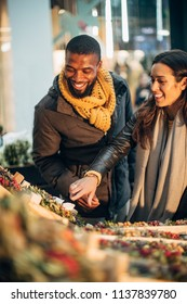 Front view of a couple standing at a christmas market stall deciding on what wreath they should buy.