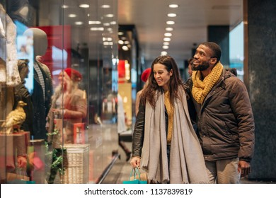 Front view of a couple walking past a shop window and looking in. They are shopping during the sales.