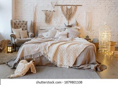 Vorderer Blick auf ein gemütliches Schlafzimmer mit weichen Decken und warmer Decke auf bequemen Betten, Kissen, Kissen, Kissen, Sessel, Wohneinrichtung und Inneneinrichtung im böhmischen Stil